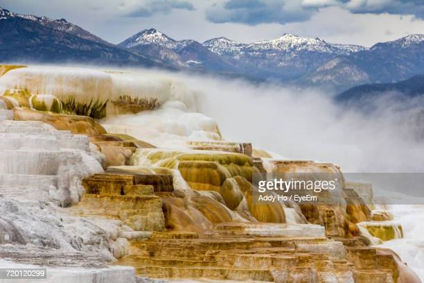 scenic view of travertine pool against mountains at mammoth hot springs - 方解石 ストックフォトと画像