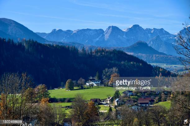scenic view of trees and buildings against mountains and sky - gerhard hagn stock-fotos und bilder