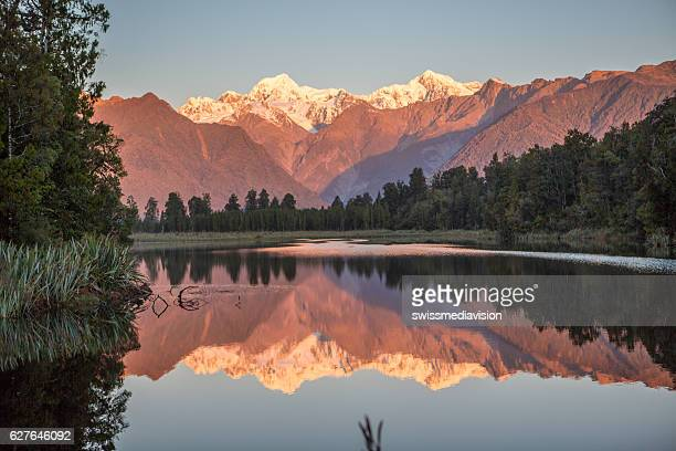 scenic view of trees and mountains reflection in lake matheson - mirror lake stock pictures, royalty-free photos & images