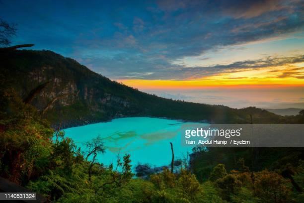 scenic view of turquoise lake by mountains against dramatic sky during sunset - tian abdul hanip stock photos and pictures