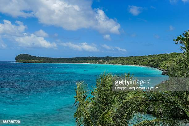 scenic view of turquoise sea against blue sky - new caledonia stock photos and pictures