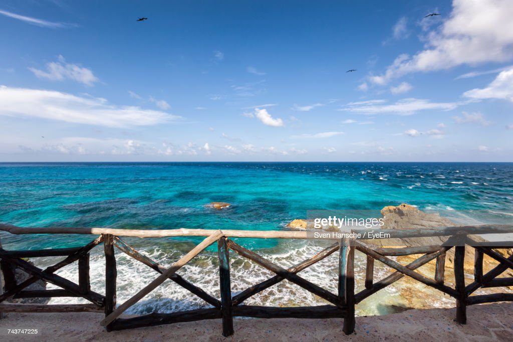 Scenic View Of Turquoise Sea Against Blue Sky Seen From Promenade : Stock Photo