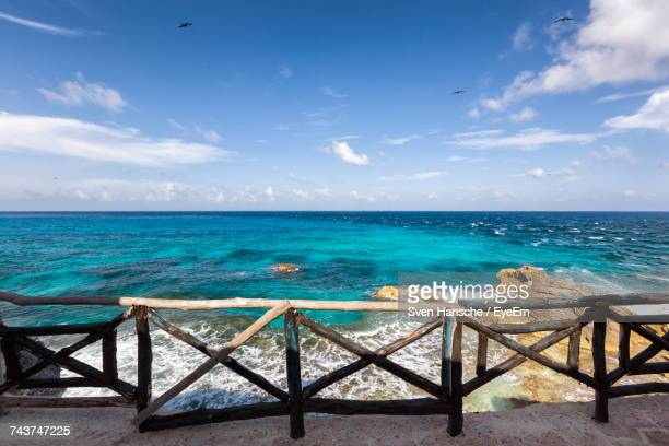scenic view of turquoise sea against blue sky seen from promenade - isla mujeres stock photos and pictures