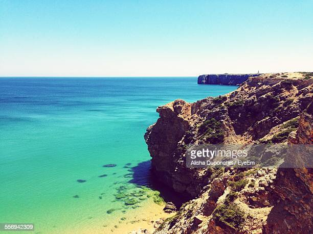 Scenic View Of Turquoise Sea By Rocks Against Clear Sky