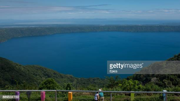 A scenic view of two tourists overlooking the Laguna de Apoyo located between Granada and Masaya Nicaragua the volcanic lake forms part of the Apoyo...