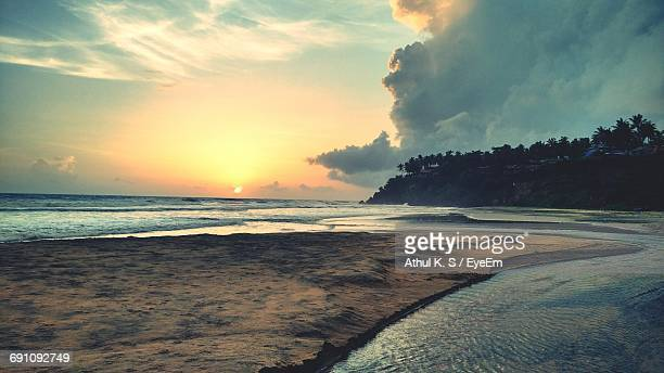 Scenic View Of Varkala Beach Against Cloudy Sky During Sunset
