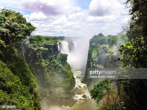Scenic View Of Victoria Falls Against Cloudy Sky