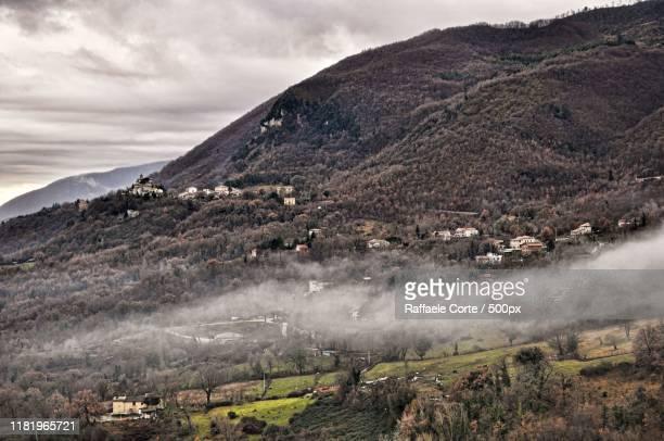 scenic view of village in mountains - raffaele corte foto e immagini stock