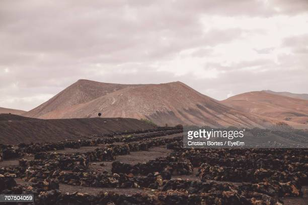 scenic view of volcanic landscape against cloudy sky - bortes foto e immagini stock
