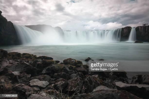 scenic view of waterfall against cloudy sky - sandra gygax stock-fotos und bilder