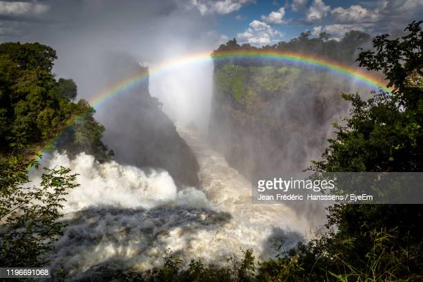 scenic view of waterfall against rainbow in sky - victoria falls stock pictures, royalty-free photos & images