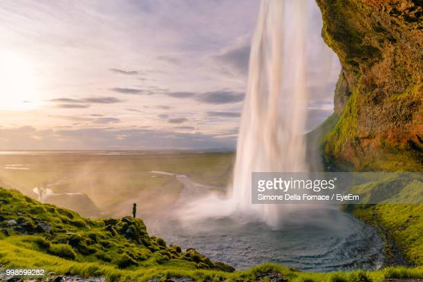 scenic view of waterfall against sky during sunset - selfoss stock photos and pictures