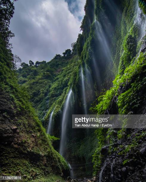 scenic view of waterfall against sky - tian abdul hanip stock photos and pictures