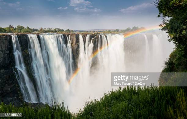 scenic view of waterfall against sky - zimbabwe stock pictures, royalty-free photos & images