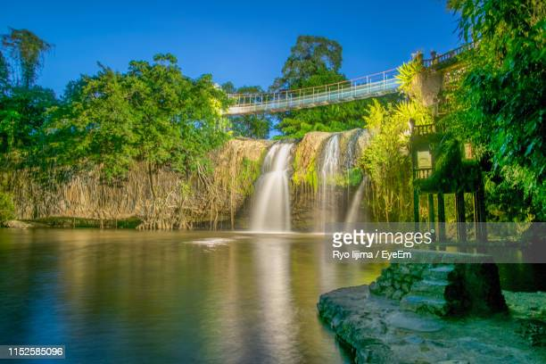 scenic view of waterfall against sky - cairns stock photos and pictures