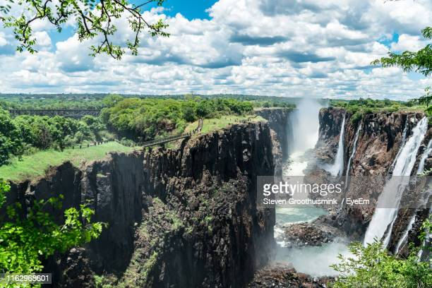 scenic view of waterfall against sky - victoria falls stock pictures, royalty-free photos & images