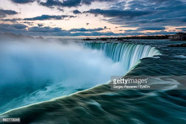 scenic view of waterfall against sky - niagara falls stock pictures, royalty-free photos & images