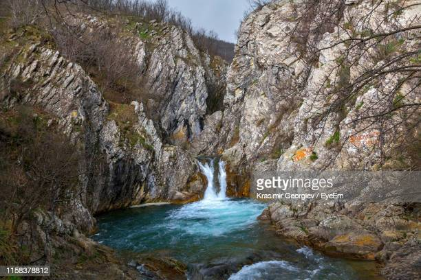 scenic view of waterfall amidst rock formations - krasimir georgiev stock photos and pictures
