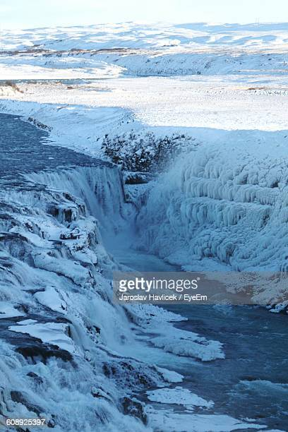 Scenic View Of Waterfall Amidst Snow Covered Field