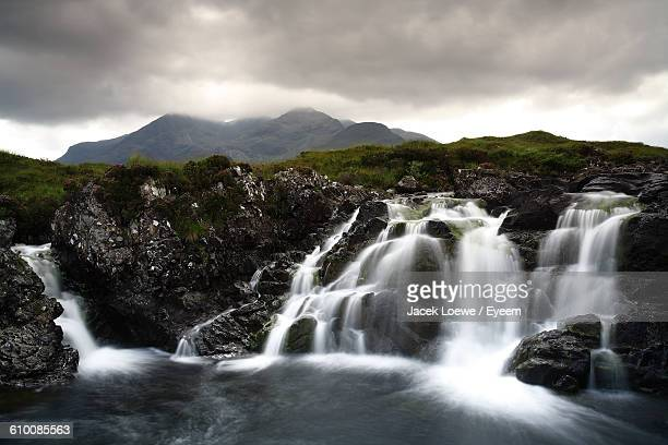 Scenic View Of Waterfall From Mountains Against Cloudy Sky