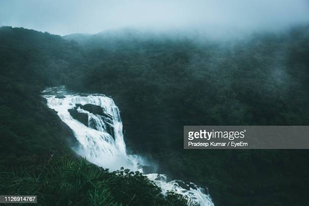 scenic view of waterfall in forest - monsoon stock pictures, royalty-free photos & images