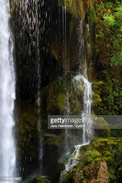 scenic view of waterfall in forest - jens helmstedt stock-fotos und bilder