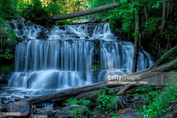 scenic view of waterfall - gerold guggenbuehl stock-fotos und bilder