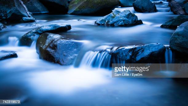 scenic view of waterfall - spring flowing water stock pictures, royalty-free photos & images