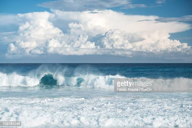 Scenic View Of Wave Splashing In Sea Against Cloudy Sky