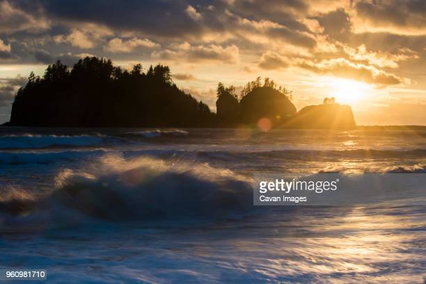 Scenic view of waves against sky during sunset