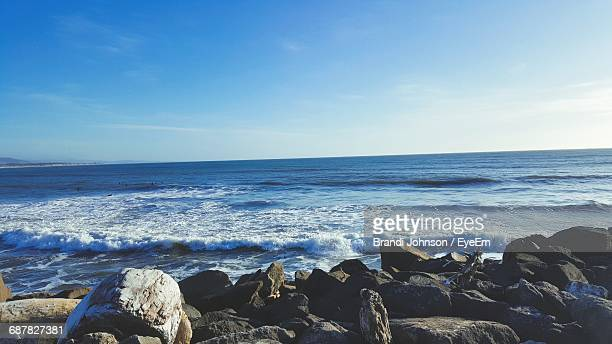scenic view of waves in sea at rocky shore against blue sky - brandi johnson stock pictures, royalty-free photos & images