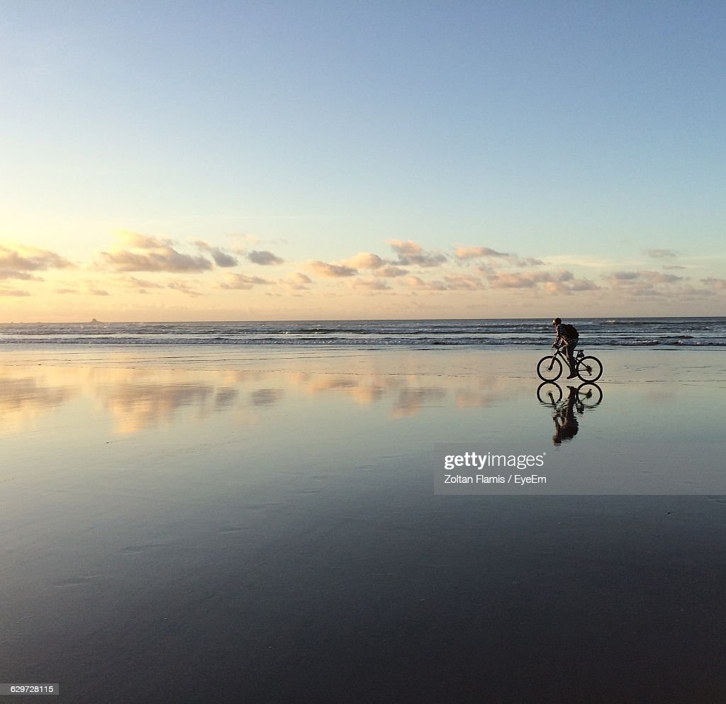 Scenic View Of Wet Beach And Sea Against Sky During Sunset : Stock Photo