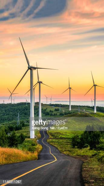 Scenic View Of Wind Turbines Against Sky At Sunset