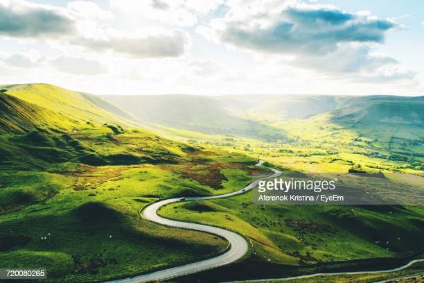 scenic view of winding road against sky - anhöhe stock-fotos und bilder