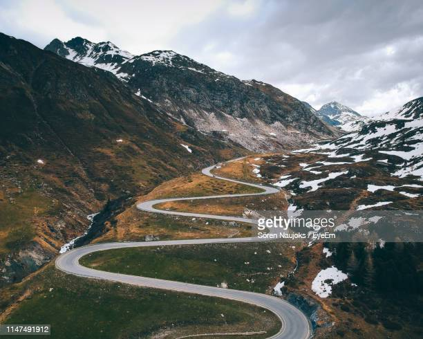 scenic view of winding road by mountains during winter - alpes européennes photos et images de collection