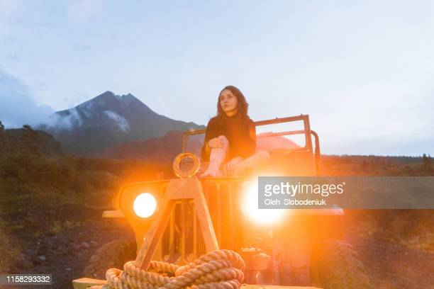 scenic view of woman sitting on old fashioned suv on the background of merapi volcano - vehicle light stock pictures, royalty-free photos & images