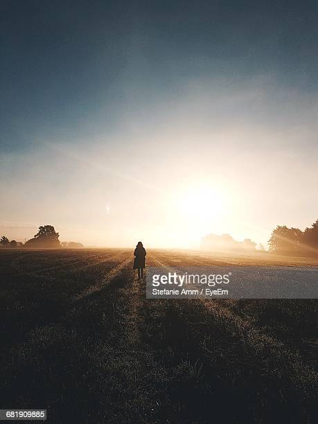 Scenic View Of Woman Walking On Empty Field At Sunrise