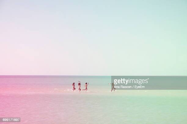 Scenic View Of Women In Sea Against Sky