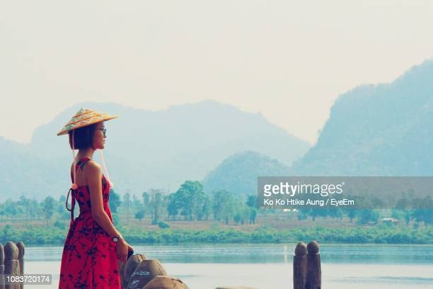 scenic view of young woman standing by lake against sky - ko ko htike aung stock pictures, royalty-free photos & images