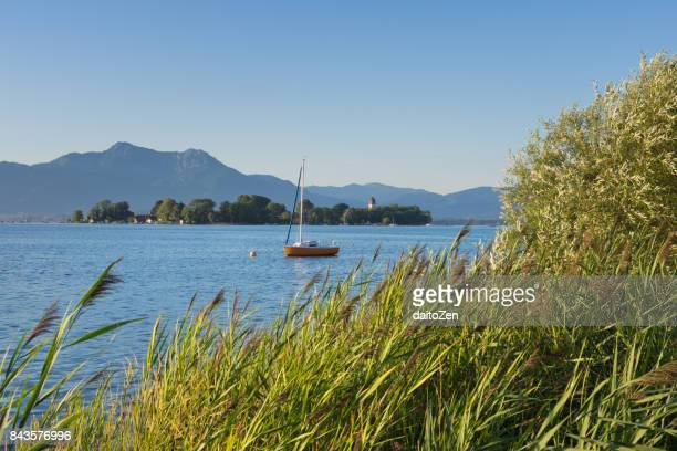 Scenic view over Lake Chiemsee with sailboat in front of island Frauenchiemsee, Bavarian Alps in the distance, Chiemgau, Upper Bavaria, Germany