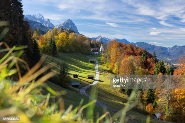 Scenic view over road leading to Wamberg village with Zugspitze and Wetterstein mountain range in the background, Werdenfelser Land, Upper Bavaria, Germany