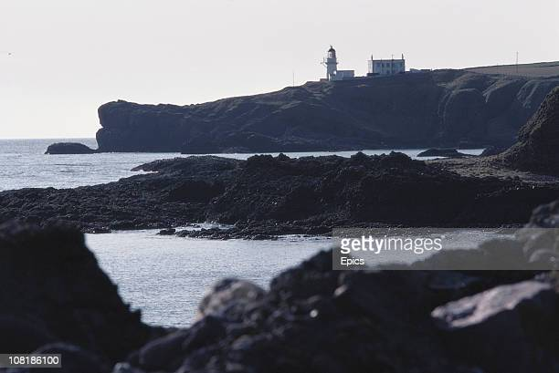 Scenic view to the lighthouse along the coast at Tod Head Point, Catterline, Aberdeenshire, Scotland, October 1982.