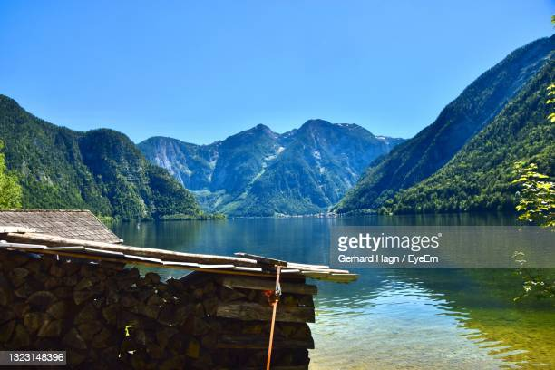 scenic view with boathouse, lake and mountains against clear blue sky - gerhard hagn stock-fotos und bilder