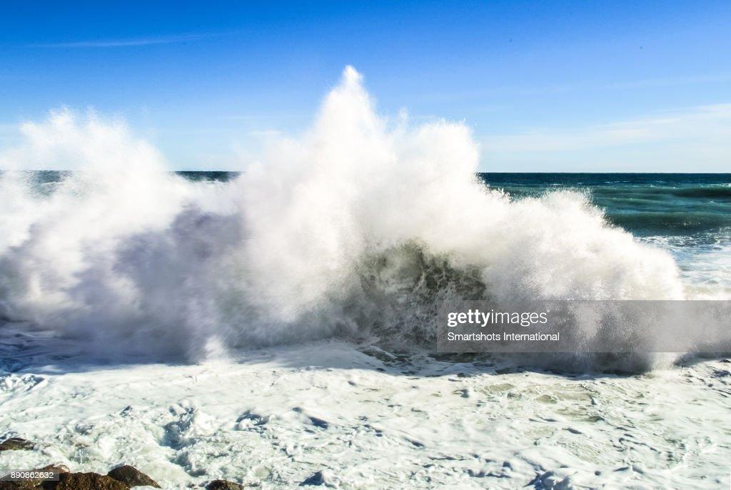 Scenic wave breaking at high tide in the Mediterranean sea near Genoa, Liguria, Italy : Stock Photo