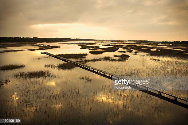 Scenic wooden walkway stretching over wetlands at sunset on Bald Head Island, North Carolina
