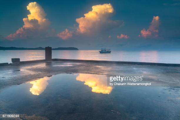 Scenics morning sky and reflection with Fishing Boat Mooring in the Blue Sea.