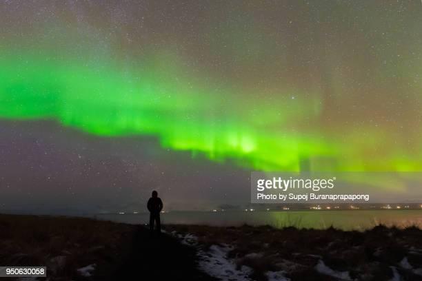 Scenics of aurora borealis or aurora polaris in the sky.Photographer standing under aurora light phenomenon in winter of iceland