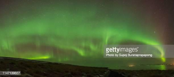scenics view of aurora borealis phenomenon dramatic sky in iceland. - light natural phenomenon stock pictures, royalty-free photos & images