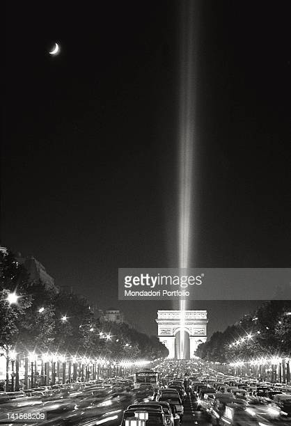 Scenographic light to the sky in Place de l'Etoile in front of the Arch de Triomphe photographed by the ChampsElysTes with the streets crowded with...