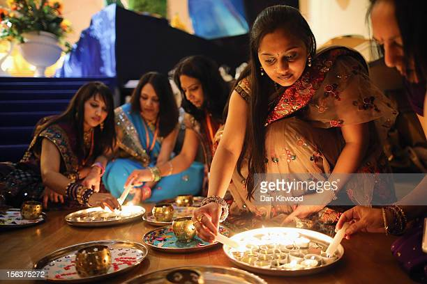 Scented candles are lit before being offered to wellwishers during a ceremony as Sadhus and Hindus celebrate Diwali at the BAPS Shri Swaminarayan...